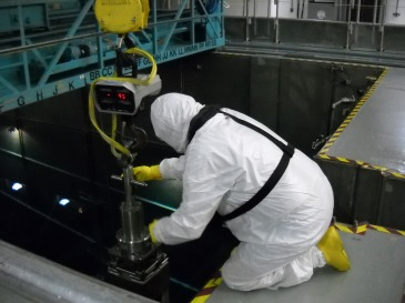 A member of the fuel team helps guide a new fuel assembly into the used fuel pool.