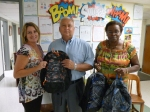 Robinson Nuclear Plant senior manager Warren Farmer poses for a photo with school officials receiving book bags