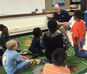 Children at Cain Elementary gather around to hear Robinson team member Bruce Douglas read.